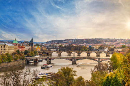 The sun is setting behind the horizon, Prague's river and its bridges in the foreground