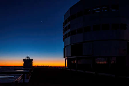 Silhouette of VLT and auxillary telescope during sunset