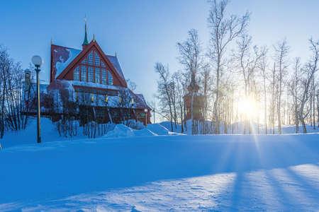 Kiruna church or Kiruna kyrka with the sun slowly setting behind trees Archivio Fotografico
