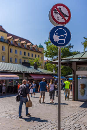 Official sign at Viktualienmarkt reminding everyone wearing face mask