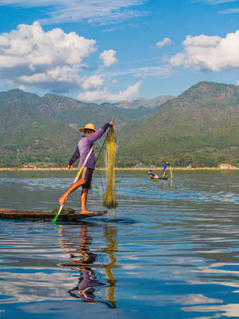 Inle Lake, Myanmar - January 4, 2018: Young Burmese Fisherman Paddling a Boat With One Leg While Using His Fishing Net Archivio Fotografico