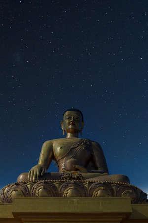 Giant golden Buddha at night with stars above- Thimphu, Bhutan Archivio Fotografico