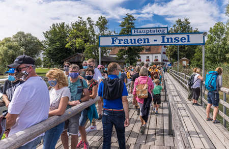 Fraueninsel, Germany - August 31, 2020: People with protective facemasks wainting in line for a boat to at the tourist destination Chiemsee lake in Bavaria - Germany