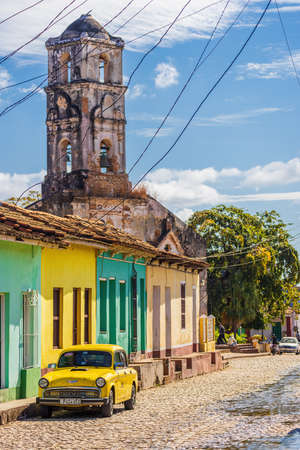 Colorful houses with the tower of the church Iglesia de Santa Ana in Trinidad, Cuba