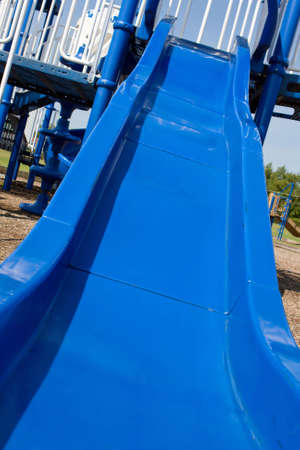 Blue slide attached to a large playground.