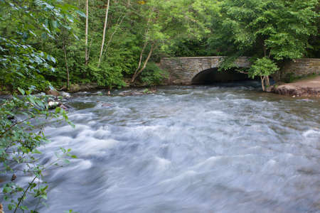 rushing water: Rushing water of a creek goes under the arch bridge.