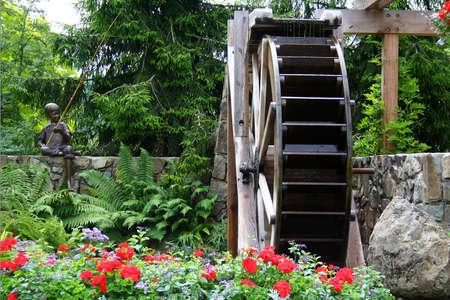 Waterwheel in a spring time Flower Garden.