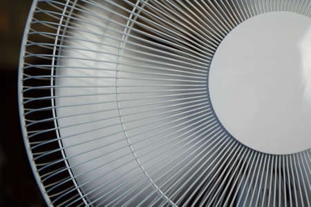 oscillate: blades in motion creating a breeze from a white house fan. Stock Photo
