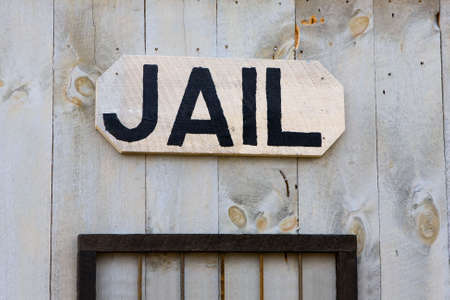 jail: An old-fashioned Western jail sign hanging on a wall. Stock Photo