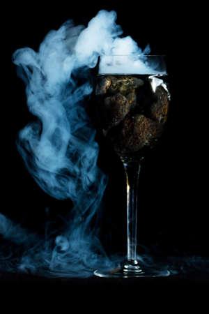 Smoking wine glass with lava rocks.