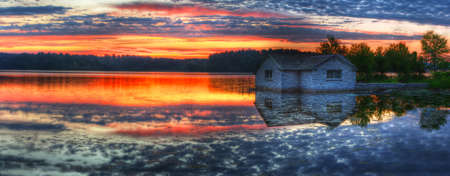 Panorama of a sunrise and pump house utility on a lake. Imagens