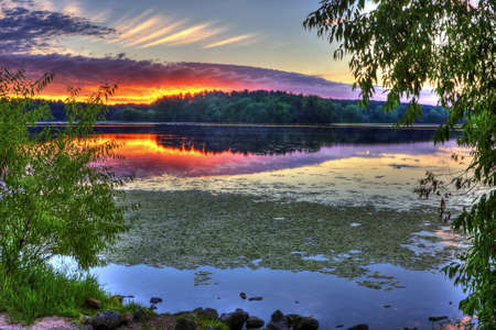 Beautiful sunrise on a lake framed by trees photo