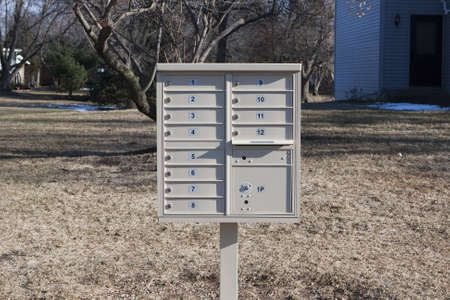 postmaster: Group of mailboxes are in an arrangement in a residential neighborhood.