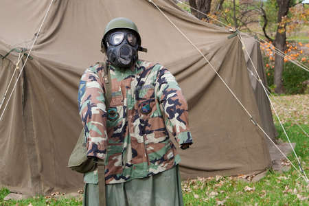 Dummy in a gas mask near a tent. photo