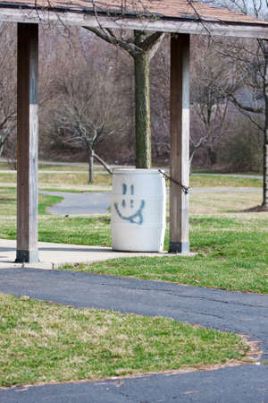 Garbage Bin at a park with a smile  photo