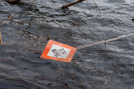 Thin Ice sign in water on lake