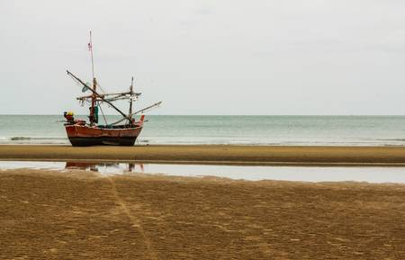 Fishing boat moored on the beach photo