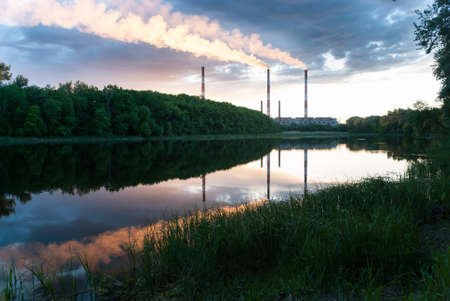 Pipe coal-fired power plant on the background of the river and evening sky Stock Photo