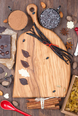 Wooden board with prepared to sweet chocolate baking ingredients  Top view