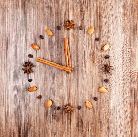 Clock face on a wooden background of almonds and coffee beans with arrow of cinnamon sticks