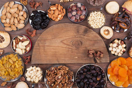 Wooden semi-circle, surrounded by nuts and fruits Stock Photo