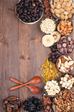Frame of variety of fruits and nuts on a dark wooden surface photo