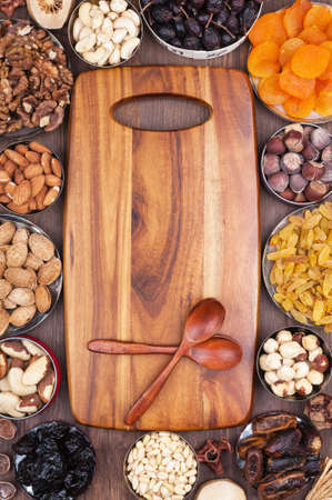 Wooden kitchen board surrounded by ingredients photo