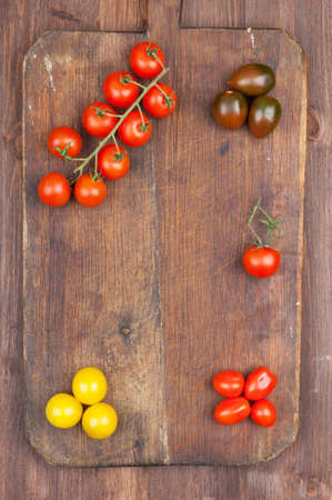 cherry varieties: Set of different varieties of cherry tomatoes on a dark wooden background