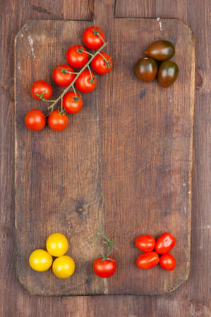 Set of different varieties of cherry tomatoes on a dark wooden background