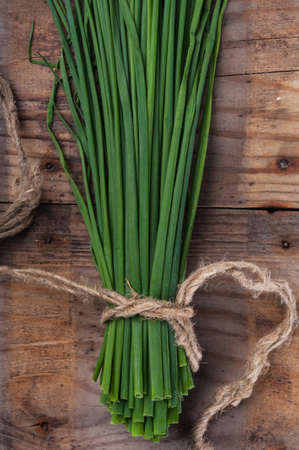 Bunch green onion chives, tied with a rope on the old wooden surface photo