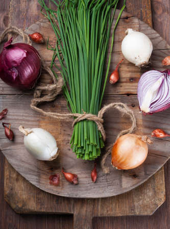 Different varieties of onions on a round kitchen board and wooden surface