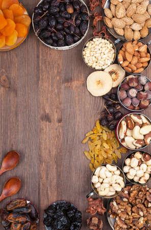 frutos secos: Marco de la variedad de frutas y nueces sobre una superficie de madera oscura