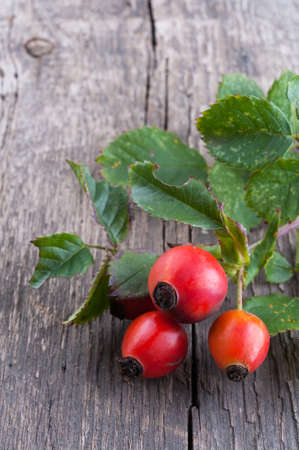 Rosehip berries on a old textured wooden background