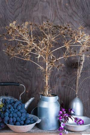 Kitchen utensils on the wooden background with dry autumn prairie flowers