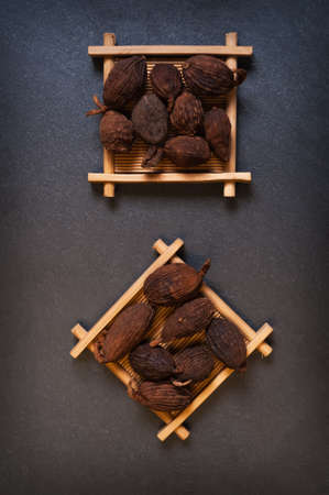 Chinese black cardamom on a black background Stock Photo