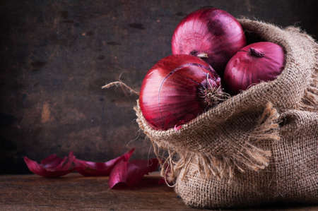 Sweet red onions in a canvas bag on a wooden surface