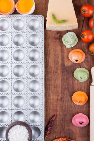 Form for cooking and multicolored ravioli on a wooden board