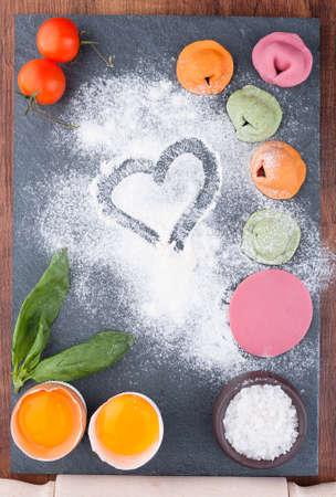 Homemade multicolor ravioli with vegetables on a slate blackboard Stock Photo