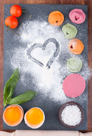 Homemade multicolor ravioli with vegetables on a slate blackboard Stockfoto