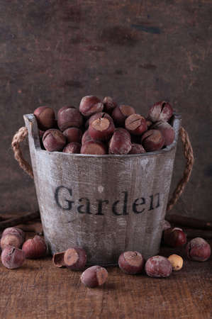 unpeeled: Unpeeled hazelnuts in a wooden bucket with the words  garden