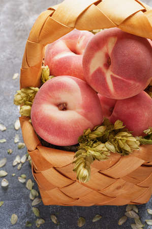 textural: Wicker basket with juicy peaches on a gray textural background