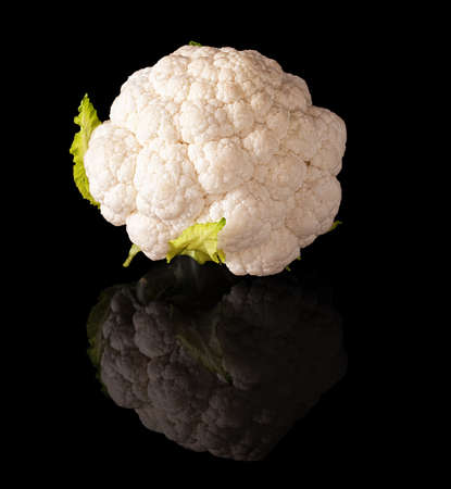 coliflor: Coliflor aislado en un fondo negro brillante con la reflexión verdadera