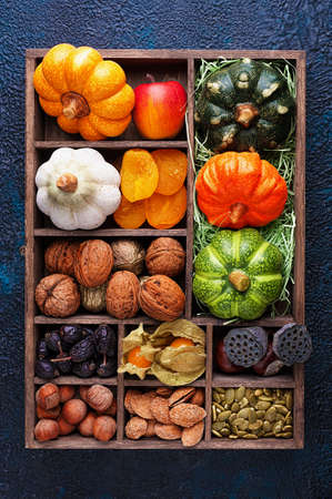 Set of autumn vegetables, fruits, nuts and seeds in a wooden box with cells top view