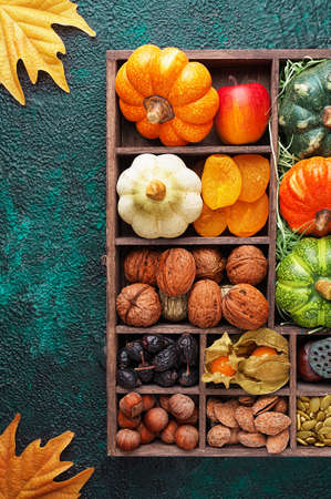 Set of autumn vegetables, fruits, nuts and seeds in a wooden box with cells top view with copy space
