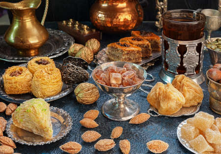 Large set of Eastern, Arab, Turkish sweets with cup of tea Stock Photo