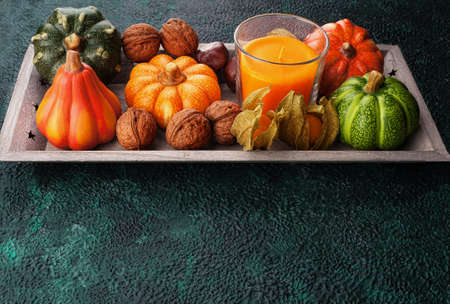 Tray with autumn harvest on textural background with copy space