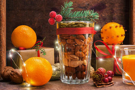 Christmas decoration glass with a variety of nuts on a wooden background Stock Photo