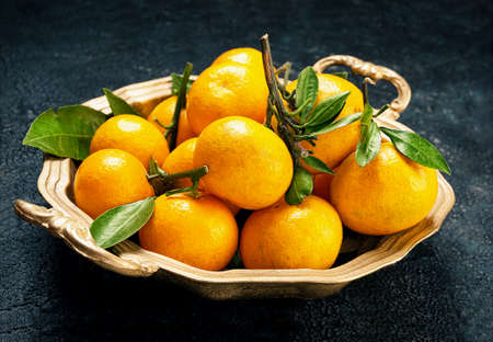 Tangerines on a round platter and texture background
