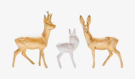 Male, female and young deer in gold and silver color carved in wood isolated
