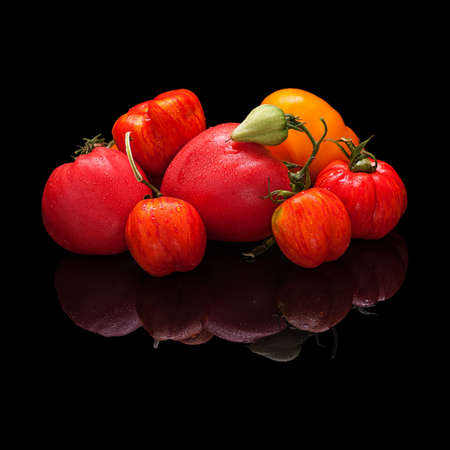 Large group of multi-colored tomatoes isolated on a black glossy background with a real reflection Stock Photo